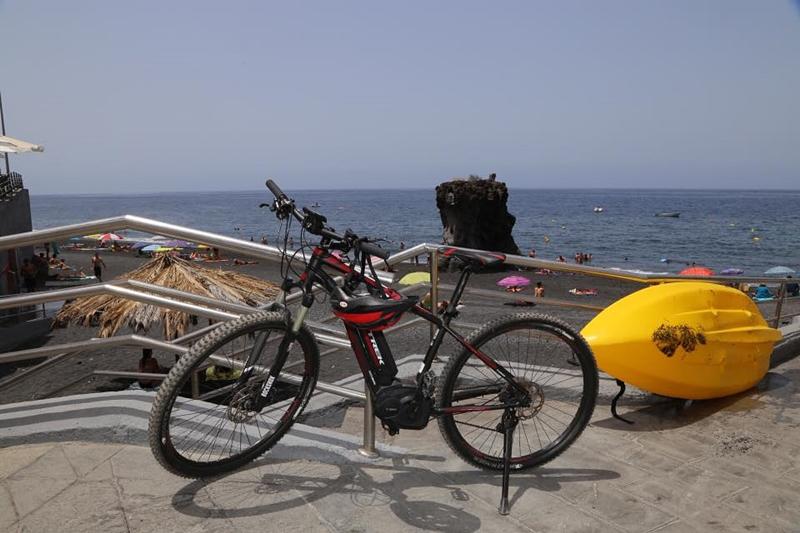 Sommerdunst und Hitze wabern über La Palma: Es gibt dennoch ganz Harte, die bei diesem Wetter radeln - andere ziehen kühleres Ocean-Kajaking vor. Allerdings handelt es sich bei dem Rad um ein E-Bike von La Palma 24, mit dem man selbst noch bei Temperaturen um die 30 Grad relativ entspannt über die Insel kommt. Foto: Michael Kreikenbom