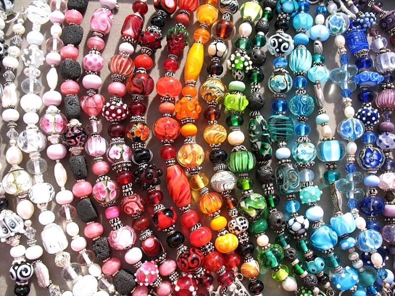 """Glaskünstlerin Cornelia Spork jetzt auch im Princess. Viele kennen die handgefertigten """"Juwelen"""" aus Glas von Cornelia Spork, und jetzt hat die Kunsthandwerkerin einen weiteren Verkaufsstandort ins Programm genommen: Jeden Mittwoch baut sie ihren Stand nun auch im Hotel Princess im Süden von La Palma auf. Darüber hinaus kann man die Joyas de Cristal freitags von 18 bis 22 Uhr im Hotel Sol in Puerto Naos erwerben – und außerdem in ihrem noch jungen Shop in Fuencaliente namens  A mano, der direkt an der Hauptdurchgangsstraße liegt. Wichtige Info für Conny-Stammkunden: In der Markthalle in Mazo findet man die Künstlerin seit kurzem nicht mehr – sie hat ihren seit vielen Jahren betriebenen Stand wegen Arbeitsüberlastung aufgegeben. Wir haben über die Glaskünstlerin schon mal berichtet."""