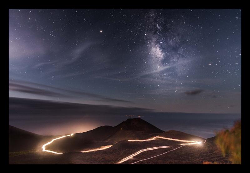 2018: Diese Aufnahme soll der krönende Abschluss unseres Ausflugs in die Welt der Sterne über La Palma sein. Es ist das Siegerfoto des ersten Transvulcania Photo Contests 2018 von Adrián García Rivero aus Gran Canaria. Er hatte sich oberhalb des Vulkans Teneguía plaziert, wodurch es ihm gelang, sowohl die Leuchtspur der Tailrunner-Stirnlampen als auch das Starlight über dem Skyrunning-Event – und sogar die Lichter von El Hierro ins Bild zu bannen.