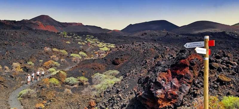 """Lob für Mondlandschaft im Süden. Der Reiseblog El Viajero der spanischen Tageszeitung El País hat den Vulcan Teneguía an der Südspitze von La Palma unter """"die zwölf beeindruckendsten Landschaften aus Meer und Fels an der spanischen Küste"""" gewählt. Der Viajero-Redakteur hat diesen Artikel mit dem Titel """"Spaziergang durch die Unterwelt"""" gewürzt. In diesem Reiseblog wurde die Isla Bonita schon öfter mal lobend erwähnt. Zum Beispiel in der Serie """"15 europäische Paradiese ohne Massentourismus"""", in einer Veröffentlichung über """"die zehn idealen Ziele für Freunde der Wissenschaft"""" mit Blick auf die Observatorien oder bei der Wahl der """"zwölf spaßigsten Karnevalevents in Spanien""""."""