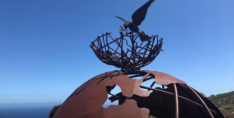 """Neuer Aussichtpunkt in Garafía. Am vergangenen Wochenende wurde der Mirador de la Paz in Garafía eröffnet. Blickfang ist eine Skulptur von Eleno Martín Rodríguez, die der Künstler seiner Geburtsgemeinde gestiftet hat. Das Kunstwerk stellt die Erde dar, über der ein Nest und Taube den Begriff """"Frieden"""" im Namen des Aussichtspunktes symbolisieren. Bei der Einweihung waren neben Bürgermeister Martin Tano unter anderen auch Inseltourismusrätin Alicia Vanoostende anwesend."""
