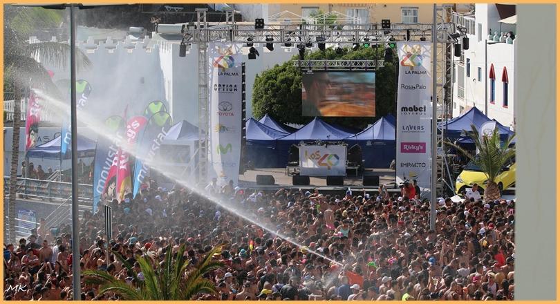 Wasserfest in Puerto Naos. Am Samstag, 21. Juli 2018, bleibt in Puerto Naos wieder kein Auge trocken: Um 15 Uhr werden auf der Strandpromenade des Badeorts die Wasserhähne aufgedreht, dazu dröhnt Musik von der Bühne, auf der sich Sternchen der Pop-Szene und DeeJays versammeln. Nichts für Leute mit Lautstärke-Problemen oder Wasserscheu.