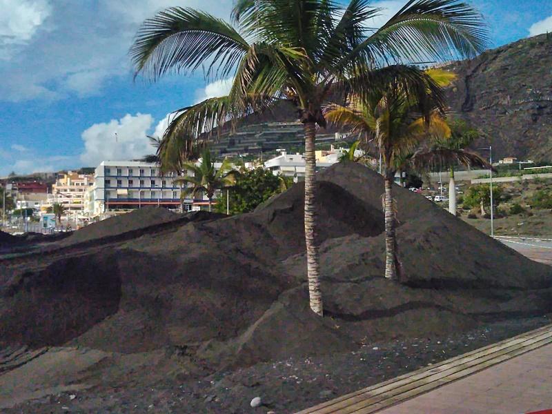 """Die neuen """"Berge"""" von Puerto Naos. In den vergangenen Tagen sah man Laster mit Sand vom Strand in Tazacorte zur Playa von Puerto Naos fahren, wo die schwarze Fracht abgeladen wurde. """"Roque Puerto Naos"""", witzelte Steven von der WhatsApp-Gruppe Fotografía Puerto Naos, als er Aufnahmen von den so entstandenen """"Bergen"""" veröffentlichte. Los Llanos-Stadtrat Mariano Zapata brachte im Zuge der darauf entbrannten Diskussion, warum Sand an den Strand gekarrt werde, Licht ins Dunkel: Bei den Bauarbeiten am Kai im Hafen von Tazacorte sei eine Menge davon angefallen, und die Küstenbehörden wussten nicht, wohin damit. Man habe sich daraufhin entschieden, ihn nach Puerto Naos zu bringen, weil er hier nicht störe."""