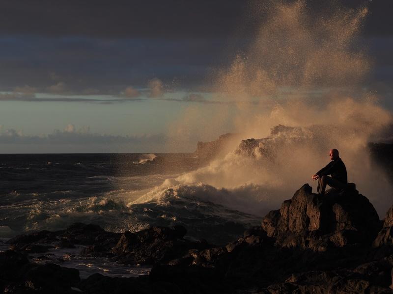 """Fels in der Brandung. Wir hatten auf der Insel ja öfter mal richtig Welle in den vergangenen Wochen, und Guido Lach aus Berlin auf seinem gischtumsprühten Felsenthron zum ersten Foto der Woche im Dezember 2018 gewählt. Denn auch er erlebte den Ansturm der Wogen im vergangenen Winter des Öfteren als er drei Monate im Süden in Las Indias verbrachte: """"Am 9. Januar 2018 schoss meine Frau Christiane dieses Foto von mir an der Playa Puntalarga, und dieses Jahr werden wir in Las Manchas überwintern, denn La Palma ist einfach eine geniale Insel."""" Im Blick auf dieses Foto der Woche raten wir Inselgästen allerdings: Nicht nachmachen! Denn solche Schnappschüsse in der Brandung sind alles andere als ungefährlich.  Wie ausgelobt haben wir nun aus den Fotos der Woche das Siegerbild des Monats gewählt. Und das Voting des La Palma 24-Teams ergab eine Überraschung: Nach der Vergabe der Punkte stellte sich heraus, dass zwei Fotos der Woche gleichauf waren. Also haben wir zwei Gewinner, und zwar Thomas Pabst mit seinem Bild Regenboten im Westen und Rolf mit seinem Foto Der Tag erwacht. Die Redaktion gratuliert zum sensationellen Gewinn wahlweise einer La Palma 24-Tasse oder einem Basecap mit dem Firmenlogo! Und der Wettbewerb geht weiter: Bis Ende 2018 suchen wir aus allen Einsendungen wie bisher wieder das Foto der Woche aus - und zu Silvester wählt das Team das mit einem tollen Preis verbundene Foto des Jahres. Alle Infos dazu in unserem Artikel."""