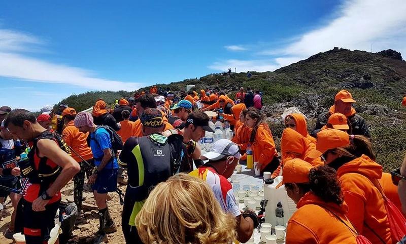 Ohne die orangeroten Freiwilligen ginge bei der Transvulcania gar nichts: Aber junge Palmeras und Palmeros machen diese Jobs gern, selbst wenn sie dabei wie hier an der Versorgungsstation am Pico de la Cruz manchmal bibbern müssen.